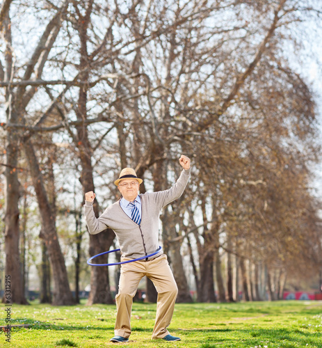 Senior man doing a hula hoop exercise in park