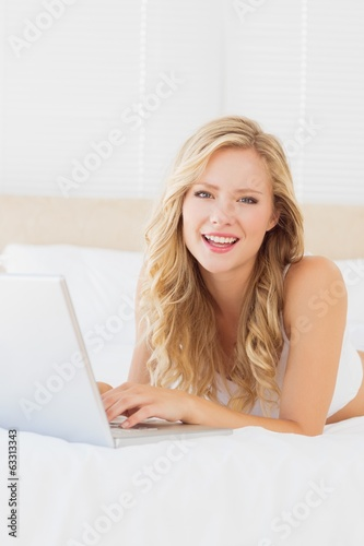 Smiling young blonde lying on her bed using laptop