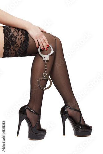 Beautiful woman legs in high heels and handcuffs