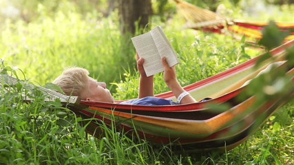 Reading last bestseller in cosy Hammock in apple trees shadows