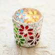 Candle burning in a colorful handcrafted container
