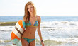 Beautiful Young Woman Surfer Girl in Bikini with Surfboard at a