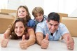 Family showing thumbs up in new house