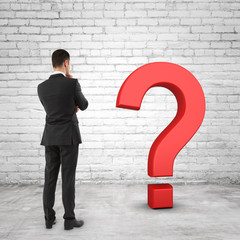 businessman looking at black question mark