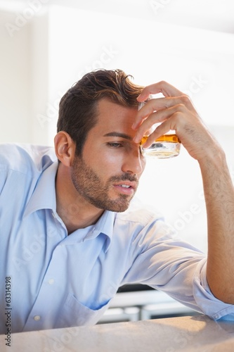 Drunk businessman clutching whiskey glass to forehead