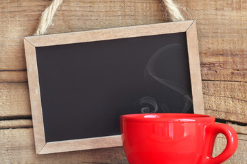 Framed vintage blackboard with a red cup of steamy coffee
