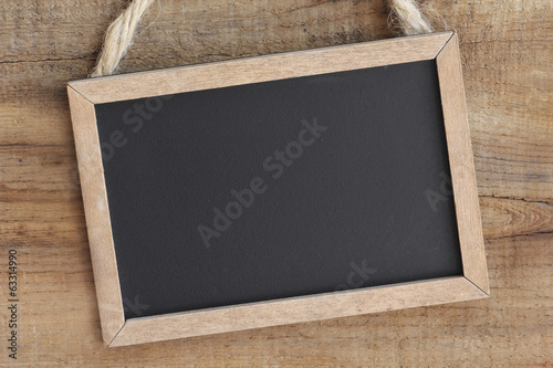 Vintage blackboard hanging on a wooden background