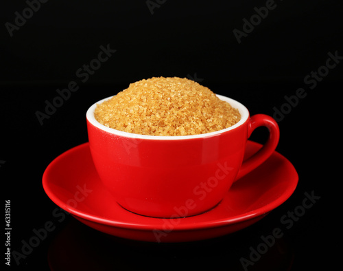 Sugar in cup isolated on black
