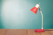 Retro red desk lamp on wooden table