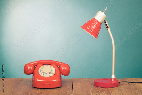 Retro red telephone and desk lamp on wood table