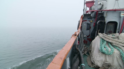 Fishing boat moving forward in the misty sea