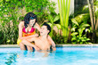 Asian couple swimming in resort pool