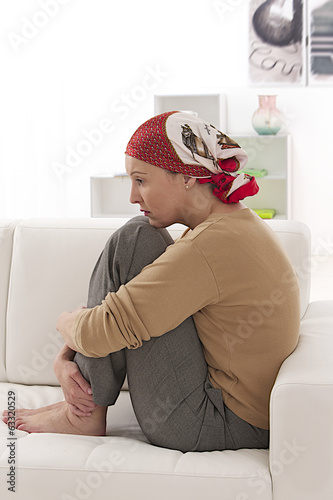 courageous  but sad cancer female patient in a head scarf.