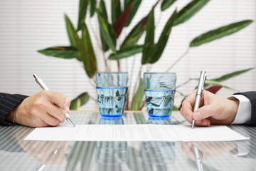 man and woman signing document with divorce or prenuptial agreem