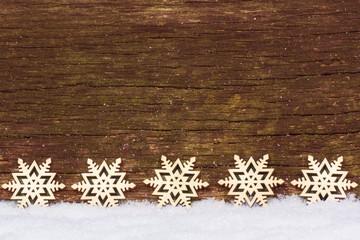 Sterne im Schnee vor Holz