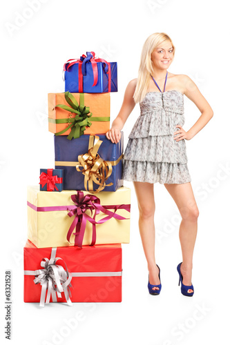 Attractive girl standing next to a pile of gifts
