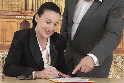 business woman signing document with business man