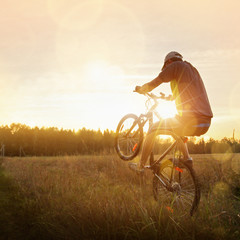 Sportsman riding a bike at sunset. Sport lifestyle