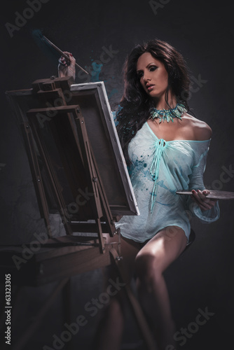 Sexy woman painting, studio shot