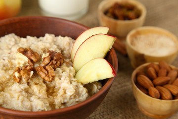 Tasty oatmeal with nuts and apples on table close up