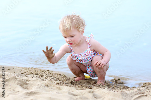 Lovely toddler girl in swimsuit playing on the beach