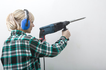 Woman in earphones holds construction tool, puncher in hand.
