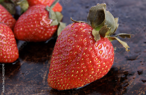 Close-up of a strawberry on rustic brown background