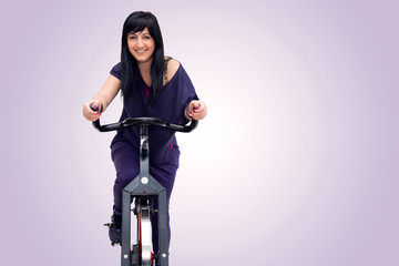 Smiling woman training on exercise bike