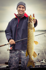 Happy angler with pike fishing trophy