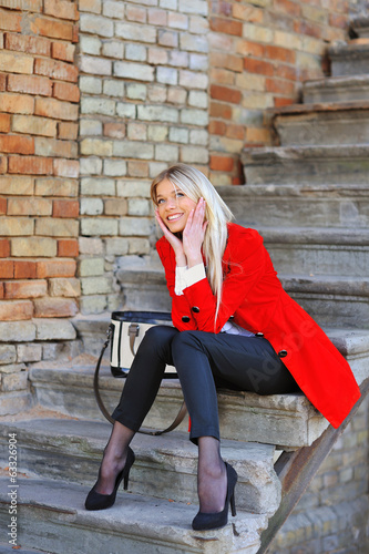 Fashionable smiling young girl in red dress with handbag outdoor