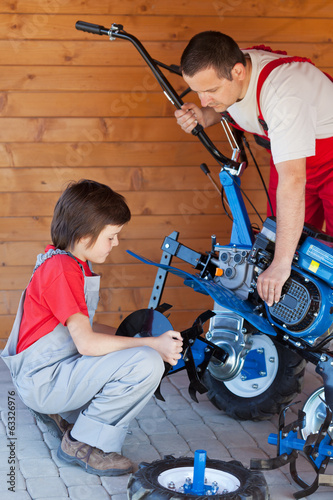Boy helps his father mounting a cultivator machine