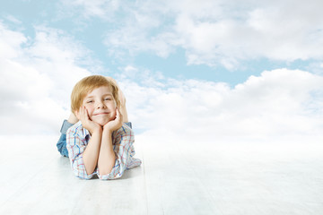 Smiling child lying down, small kid looking at camera. Blue sky