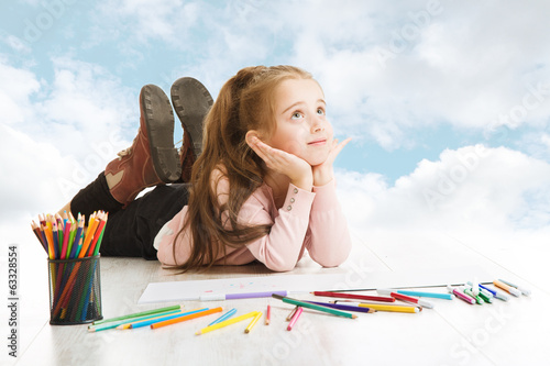 Girl dreaming, looking for drawing idea. Smiling child blue sky