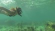 Woman snorkelling underwater in slow motion