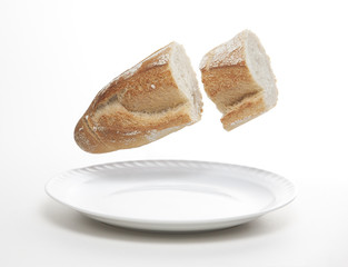 Piece of bread cut flying above a plate