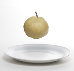 Pear levitating on white plate
