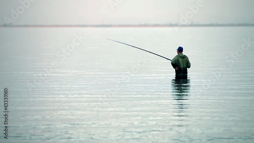 fisherman with rod  in the water fishes