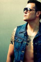 Retrato de hombre tatuado mirando.