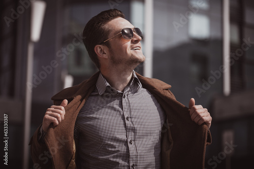 fashion man in front of a glass building wearing coat
