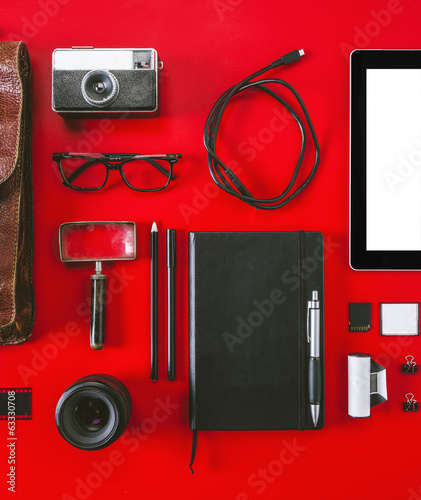 Closeup of different photography objects on red background.