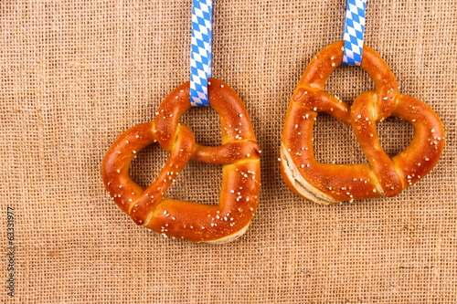Two pretzel in heart shape on jute background
