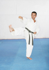 Man in a kimono hits with foot and hand.  Karate Concept