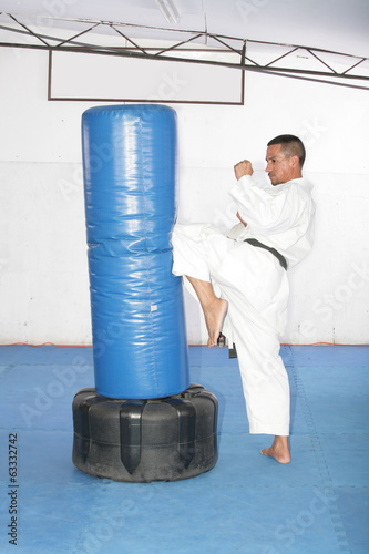 Athletic black belt karate giving a forceful knee kick during a