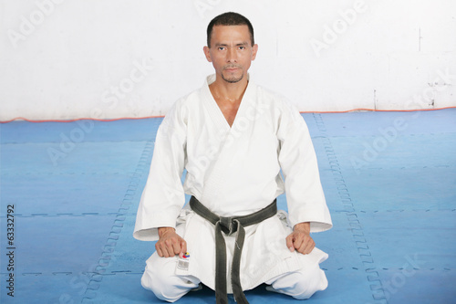 Black Belt karate man sit on a position to start or finish pract