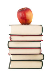 Red apple on top of a stack of books on white background