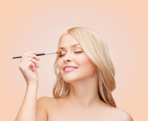 beautiful woman with closed eyes and makeup brush