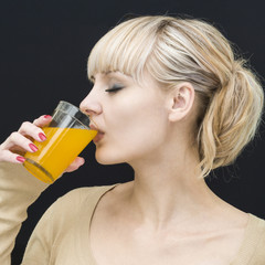 Young woman drinks juice from a glass