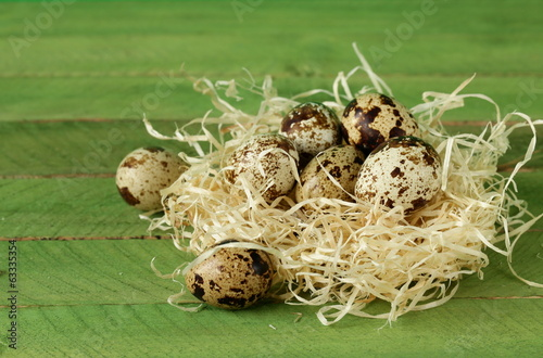 quail eggs in nest on wooden background easter still life