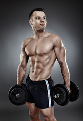 Young athletic man holding two heavy dumbbells