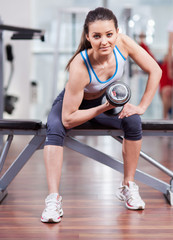 Athletic woman working her biceps with dumbbells at the gym